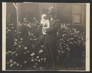 E. E. Wood and baby in front of flowering shrub