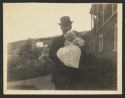 E. E. Wood and baby next to house