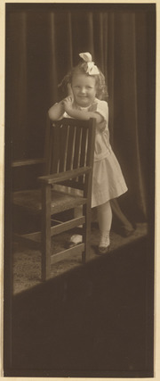 Ernestine Wood as a small child leaning on a chair